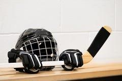 Équipement d'hockey sur le banc : Casque, gants et bâton Photo stock