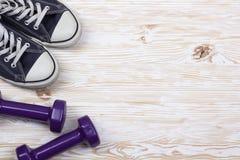 Équipement de forme physique et de sport : espadrilles, haltères sur le fond en bois Images stock