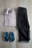 Équipement de garçon Chemise rayée, pantalon de denim et chaussures bleues sur le fond en bois gris Vue supérieure images libres de droits