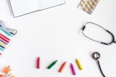 Équipement de pédiatrie avec des crayons, l'espace blanc de vue supérieure de fond de stéthoscope pour le texte Photos stock