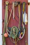 Équipement de pêche accrochant sur une porte rouge Photographie stock libre de droits