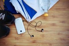 Équipement de sport Espadrilles, eau, écouteurs et téléphone sur en bois Photos stock