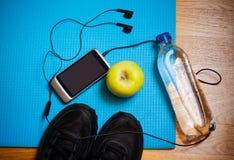 Équipement de sport Espadrilles, eau, pomme, smartphone et écouteurs Image libre de droits