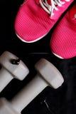 Équipement de sport sur le fond noir Folâtrez l'usage, mode de sport, accessoires de sport Espadrilles, chaussures sportives, hal Photographie stock libre de droits