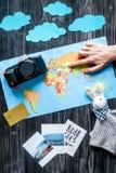 Équipement de touristes avec la carte et photos pour voyager avec des enfants sur la moquerie foncée de vue supérieure de fond  Image stock