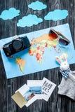 Équipement et appareil-photo de touristes avec la carte pour le voyage avec la maquette en bois foncée de vue supérieure de fond  Images stock