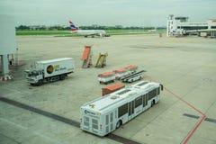 Équipement et autobus de soutien au sol attendant un avion Images libres de droits