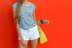 Équipement femelle d'été avec les shorts blancs courts, le T-shirt rayé et le sac jaune en cuir Beaux fille tenant le sac coloré  Photographie stock