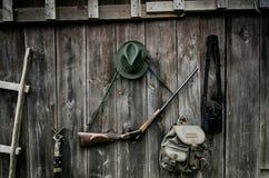 Équipement professionnel de chasseurs pour la chasse Fusil, chapeau, sac et d'autres sur un fond noir en bois photographie stock