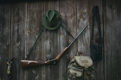 Équipement professionnel de chasseurs pour la chasse Fusil, chapeau, sac et d'autres sur un fond noir en bois photo stock