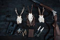 Équipement professionnel de chasseurs pour la chasse Fusil, couteaux, sculps de trophée, munitions, et d'autres sur un fond noir  images libres de droits
