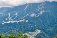 Équipements de sports et bâtiments résidentiels sur la pente d'une haute montagne avec une pente verte et le dessus dans les nuag photographie stock libre de droits