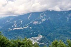 Équipements de sports et bâtiments résidentiels sur la pente d'une haute montagne avec une pente verte et le dessus dans les nuag images libres de droits
