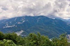Équipements de sports et bâtiments résidentiels sur la pente d'une haute montagne avec une pente verte et le dessus dans les nuag images stock