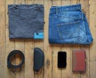 Équipements occasionnels d'hommes Chaussures, habillement et accessoires d'hommes sur le fond en bois - T-shirt gris, blues-jean, images stock