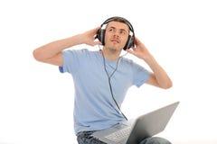 Équipez écouter la musique dans des écouteurs sur l'ordinateur Photographie stock libre de droits
