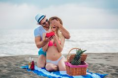 Équipez étonnant son amie avec le cadeau sur la plage Images libres de droits