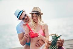 Équipez étonnant son amie avec le cadeau sur la plage Photos stock