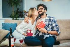 Équipez étonnant son amie avec un cadeau sur le divan Image libre de droits