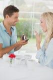 Équipez étonnant son amie avec une proposition en café Photo libre de droits