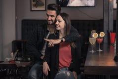 Équipez étreindre la femme, amis de couples, dirigeant le doigt, bar Image libre de droits