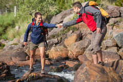 Équipez aider son amie de sourire à traverser une rivière Images stock