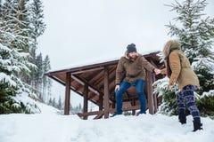 Équipez aider son amie sur des montagnes de promenade en hiver Photo libre de droits