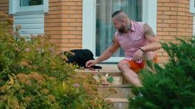 Équipez alimenter un chien avec des cerises sur le porche de maison banque de vidéos