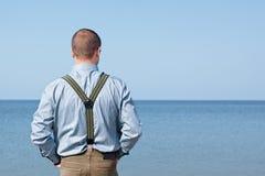 Équipez 40 ans se tenant de retour regardants la mer Photographie stock