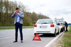 Équipez appeler tandis que dépanneuse prenant sa voiture cassée photographie stock libre de droits