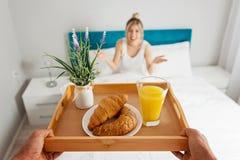 Équipez apporter le petit déjeuner à son amie dans le lit Photos stock