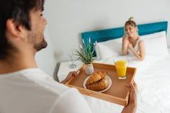 Équipez apporter le petit déjeuner à son amie dans le lit Photographie stock libre de droits