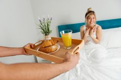 Équipez apporter le petit déjeuner à son amie dans le lit Photographie stock
