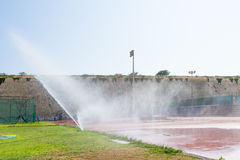 Équipez arroser d'arroseuses l'herbe des sports des gens du pays formant le stade Photos libres de droits
