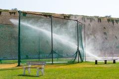Équipez arroser d'arroseuses l'herbe des sports des gens du pays formant le stade Image libre de droits