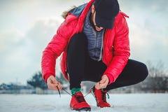 Équipez attacher une espadrille droite sur une terre neigeuse Photos libres de droits