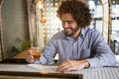 Équipez avoir le verre de whiskey dans le compteur de barre image stock