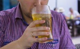 Équipez boire d'une bière froide dans la chaleur Images stock