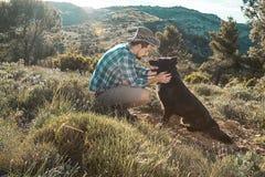 Équipez choyer son chien et jouer avec lui photographie stock