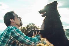 Équipez choyer son chien et jouer avec lui image libre de droits