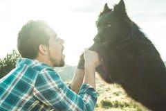 Équipez choyer son chien et jouer avec lui photo libre de droits
