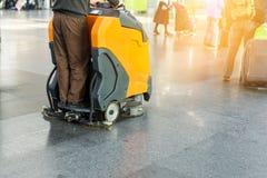 Équipez conduire la machine professionnelle de nettoyage de plancher à l'aéroport ou à la gare ferroviaire Soin de plancher et or photographie stock libre de droits