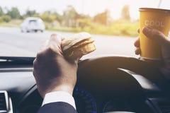 Équipez conduire la voiture tout en tenant une tasse de café froid et en mangeant l'hamburger images libres de droits