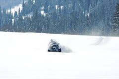 Équipez conduire le motoneige de sports dans un jour ensoleillé Photos libres de droits