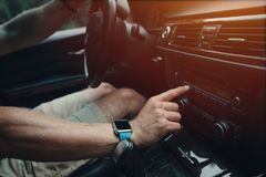 Équipez conduire sa voiture et accorder la radio, montre intelligente sur la main, à l'intérieur photo stock
