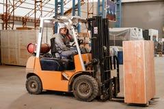 Équipez conduire un chariot élévateur par un entrepôt dans une usine conducteur dans l'uniforme et le casque de protection Le con photo libre de droits