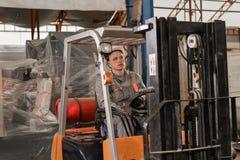 Équipez conduire un chariot élévateur par un entrepôt dans une usine conducteur dans l'uniforme et le casque de protection Le con image stock