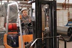 Équipez conduire un chariot élévateur par un entrepôt dans une usine conducteur dans l'uniforme et le casque de protection Le con photographie stock libre de droits