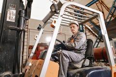 Équipez conduire un chariot élévateur par un entrepôt dans une usine conducteur dans l'uniforme et le casque de protection Le con image libre de droits