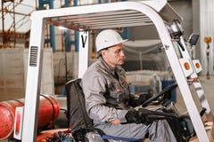 Équipez conduire un chariot élévateur par un entrepôt dans une usine conducteur dans l'uniforme et le casque de protection Le con photographie stock